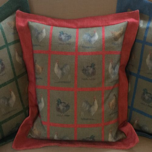 Square Chicken cushion by Blue Guinea cushion in red.