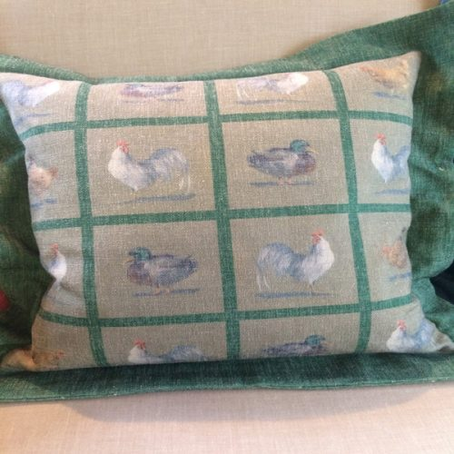 Blue Guinea square chicken cushion in green.